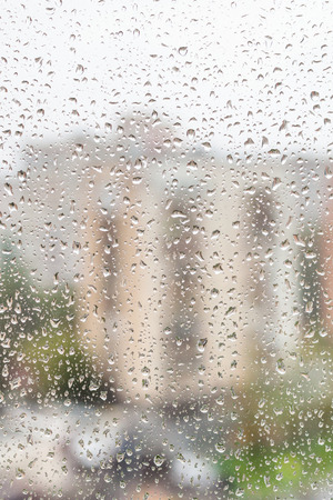 trickle down: rainy weather in city - view of raindrops on window of apartment house