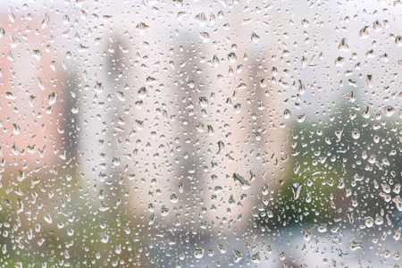 trickle down: rainy weather in city - view of rain drops on window pane of urban house Stock Photo