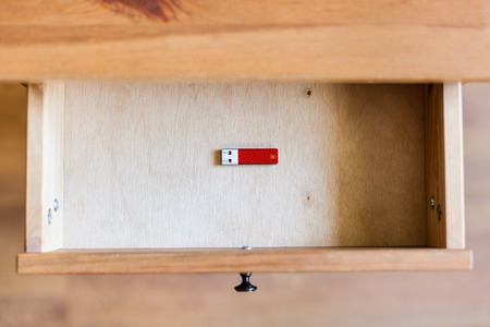 bedtable: top view of little red flash drive in open drawer of nightstand