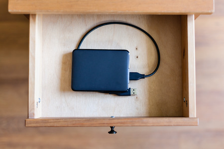 external hard disk drive: above view of external hard drive in open drawer of nightstand