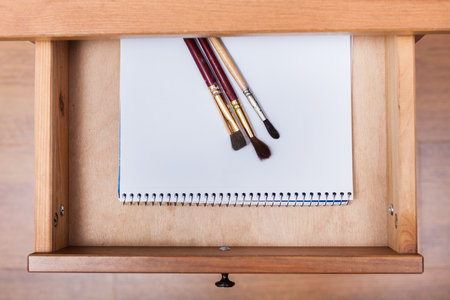 bedtable: above view of paint brushes on drawing album in open drawer of nightstand