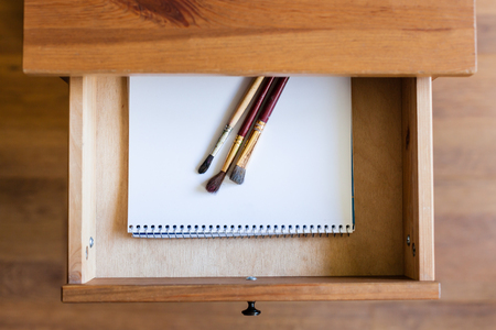 bedtable: top view of painting brushes on drawing album in open drawer of nightstand Stock Photo