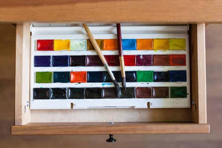 bedtable: above view of watercolor paints set and painting brushes in open drawer of nightstand