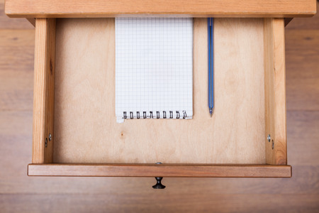 bedtable: top view of blue pen and squared notebook in open drawer of nightstand Stock Photo