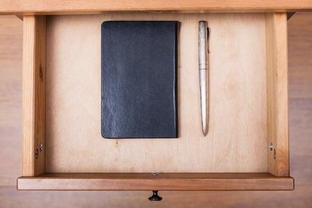 bedtable: above view of silver pen and black notebook in open drawer of nightstand