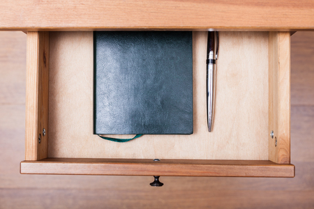 bedtable: above view of modern pen and notebook in open drawer of nightstand