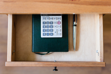 bedtable: top view of pen, calculator and notebook in open drawer of nightstand Stock Photo