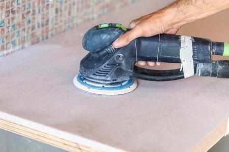 orbital: installing new tabletop on kitchen - worker sanding countertop from artificial stone by random orbital sander
