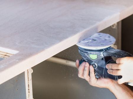 installing new tabletop on kitchen - worker sanding worktop from artificial stone by random orbital sander