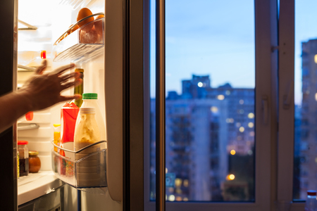 reaches: hand reaches for food in refrigerator and view of city through home window in evening Stock Photo