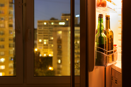 Open door of refrigerator with wine bottles and view of city through home window in night