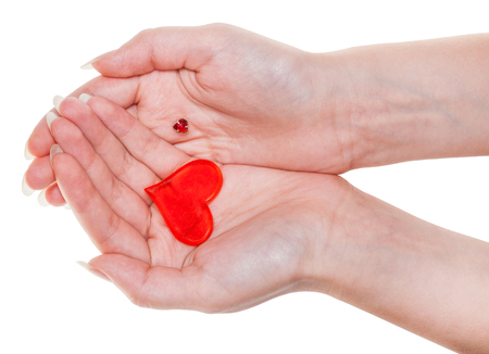 two red hearts on female palms isolated on white background