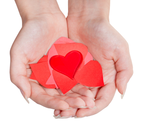 one red heart above pile of paper hearts on female palms isolated on white background