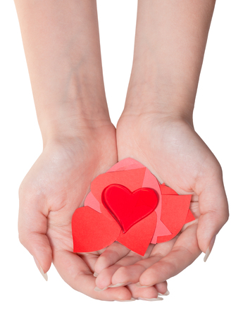 glass heart above pile of paper hearts on female palms isolated on white background Stock Photo