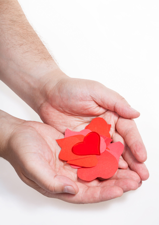 glass heart above pile of paper hearts on male palms on white background