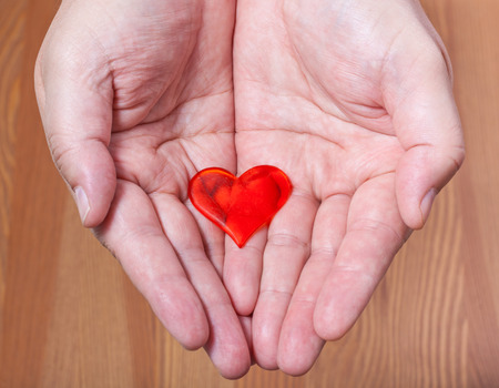 handbreadth: one red heart on male palms with wooden background Stock Photo