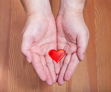 handbreadth: one red heart in male hands with wooden background Stock Photo