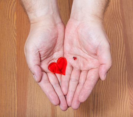 handbreadth: little and big hearts in male hands with wooden background