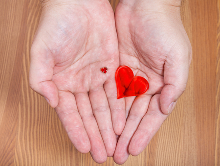 handbreadth: little and big hearts on male palms with wooden background