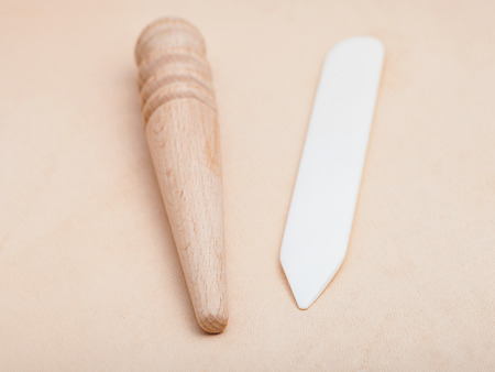 Leather crafting tool - flat plastic and round wooden slickers on natural leather Stock Photo