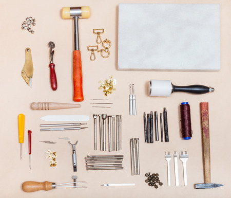 above view of set of various leathercraft instruments and marble board on natural leather surface Stock Photo