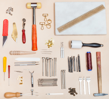 above view of set of various leatherwork tools and marble board on natural leather surface Stock Photo