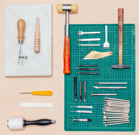 top view of various tools for leathercrafting on natural leather surface