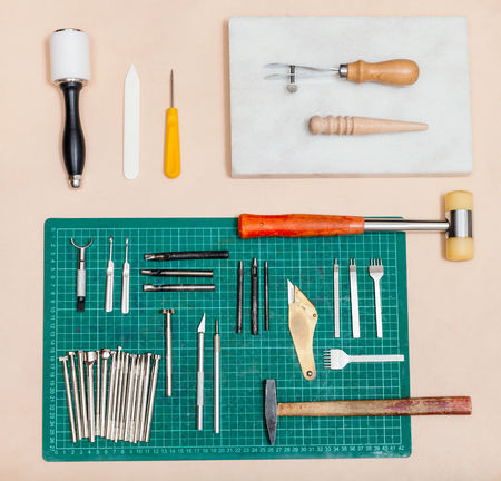 stone cutter: above view of various tools for leatherwork on natural leather surface Stock Photo