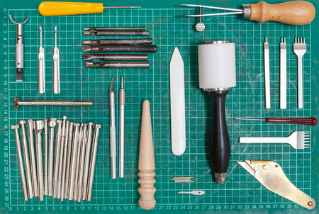 slicker: various tools for leathercraft on green self-healing mat Stock Photo