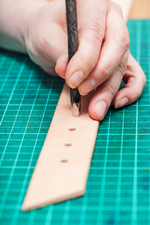 saddler: punching holes in leather belt with steel hole punch on self-healing mat Stock Photo