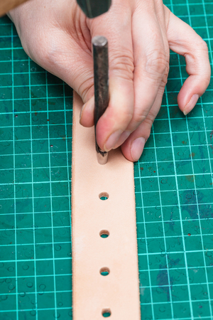 saddler: punching holes in new leather belt with hole punch on self-healing mat