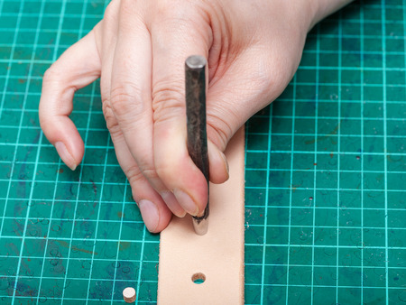 saddler: punching hole in new belt with steel punch on self-healing mat Stock Photo
