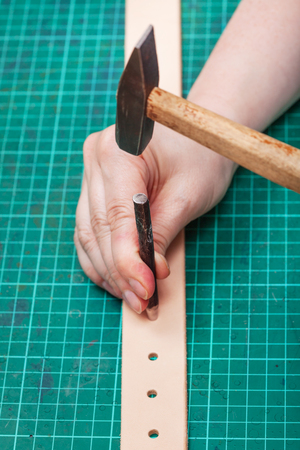 hole punch: hole punch and hammer make hole in belt on self-healing mat