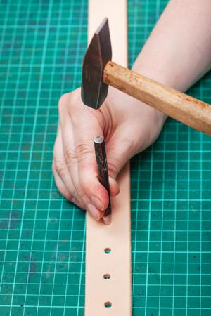 saddler: hole punch and hammer make hole in belt on self-healing mat