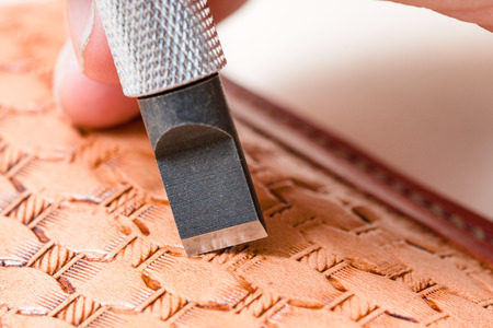 saddler: leathercrafting - blade of swivel knife carving pattern on leather close up Stock Photo