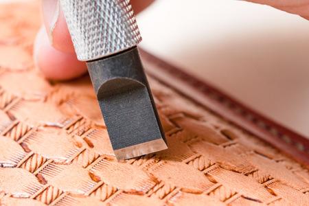 leathercrafting - blade of swivel knife carving pattern on leather close up Reklamní fotografie