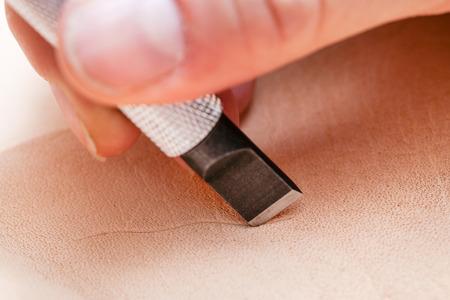 saddler: leathercrafting - blade of swivel knife carves leather close up Stock Photo