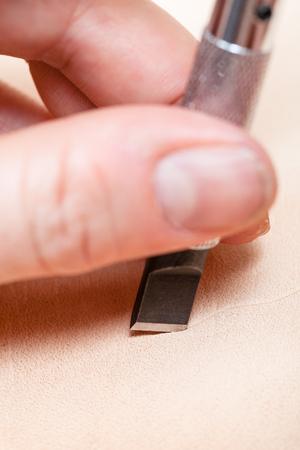 saddler: leathercrafting - blade of swivel knife cut leather close up