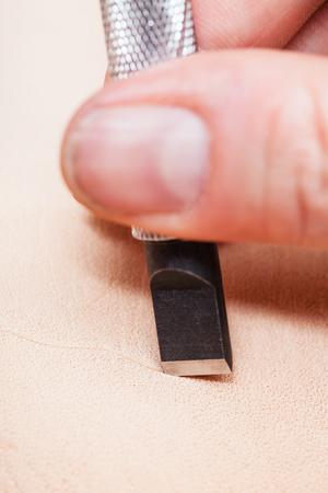 saddler: leathercrafting - blade of swivel knife cut leather surface close up