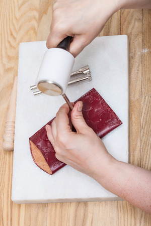 corrects: leathercrafting - craftsman corrects stamping of handmade leather pouch