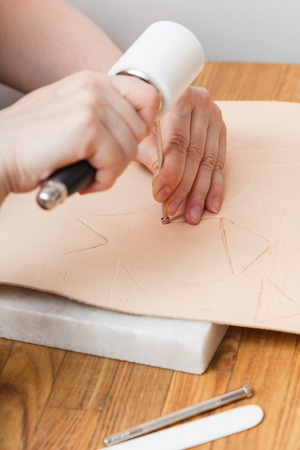 saddler: leathercraft - craftsman puts embossing on leather Stock Photo