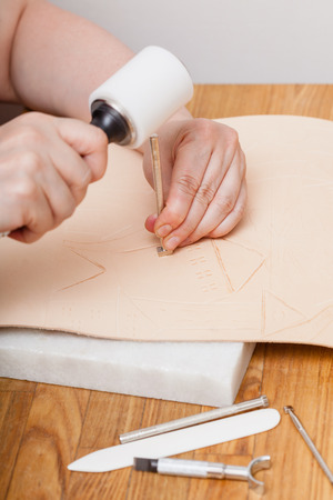 saddler: leathercraft - craftsman puts picture on leather by stamping tools