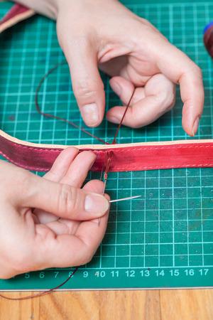saddler: leather-working - craftsman sews new leather belt Stock Photo