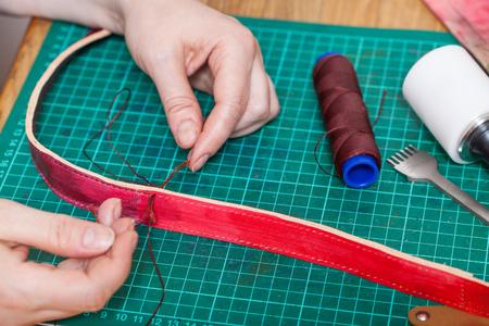 saddler: leather-working - craftsman stitches new leather belt