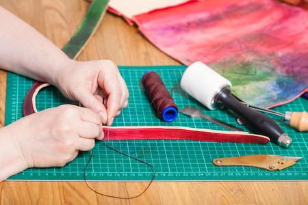 saddler: leather-working - craftsman makes leather belt for new embossed bag