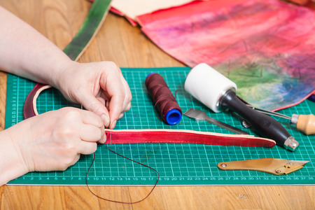 leather-working - craftsman makes leather belt for new embossed bag