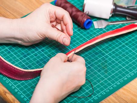 saddler: leather-working - skinner sews new leather belt Stock Photo