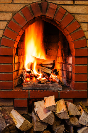 pile of firewood and firewood burning in indoor brick fireplace in country cottage
