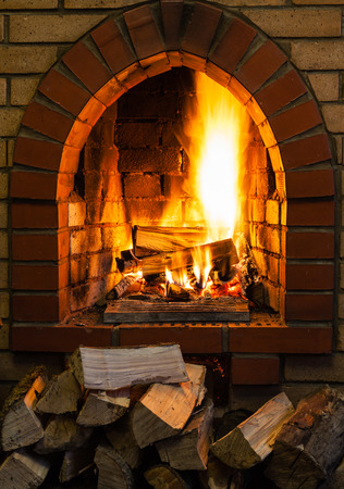 firebox: pile of wood and logs burning in indoor brick fireplace in country cottage