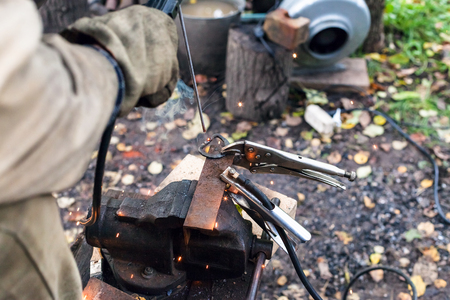 vise: Welder welds iron ring by point electric welding in outdoor rural workshop